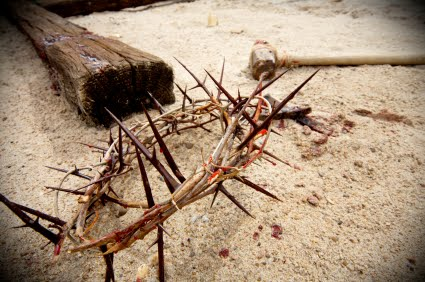 easter scene with crown of thorns, hammer and nails with blood on sand